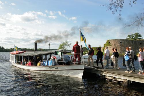 Fotografi på människor som ska gå på ångbåten Thor. I bakgrunden syns Kronobergs slottsruin