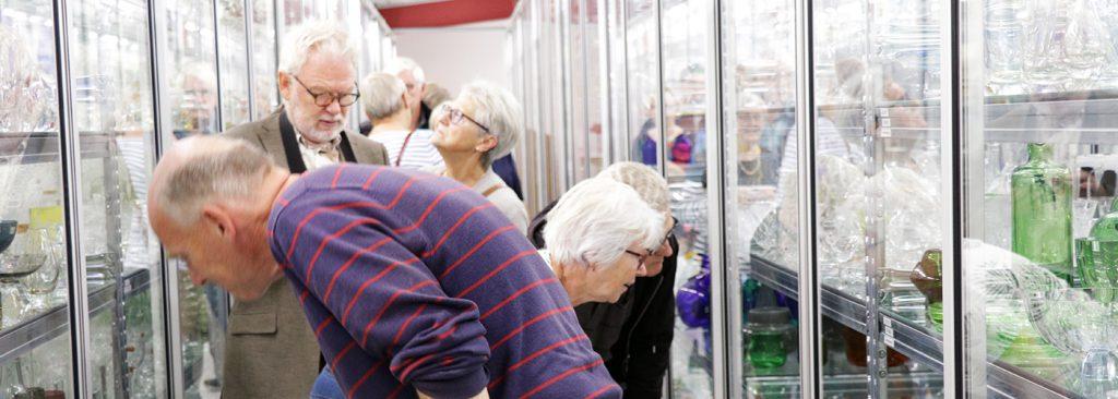 Fem personer tittar in i hyllorna med glasföremål. Bilden är tagen i det öppna magasinet på Kulturarvscentrum Småland.