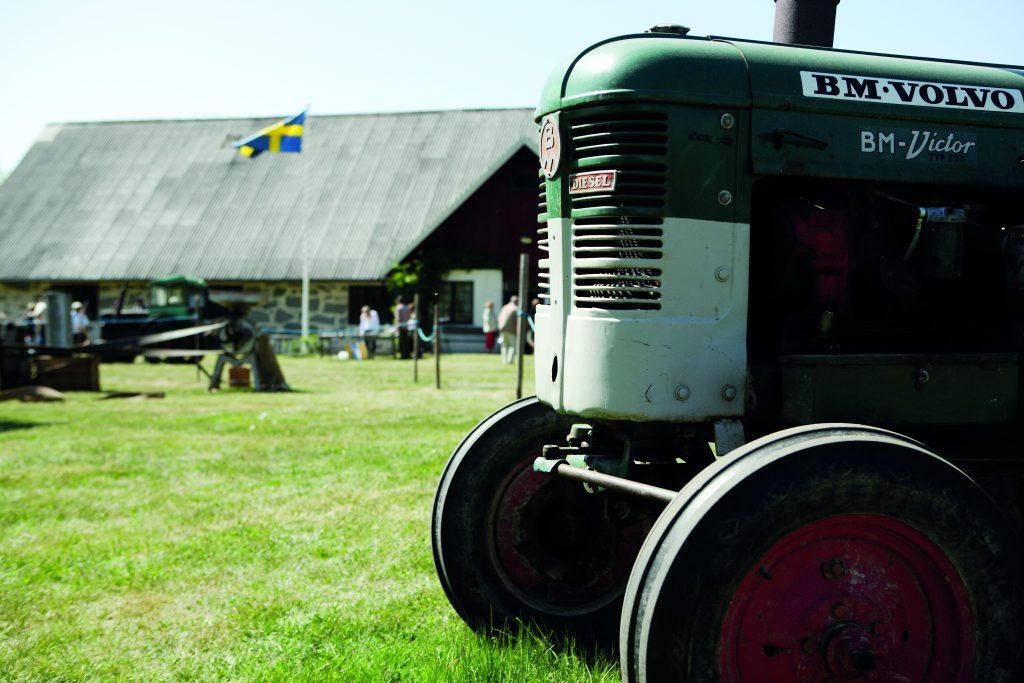 I förgrunden syns främre delen av en gammal en traktor. Den står på grönt gräs. I bakgrunden syns en röd och vit lada. En flaggstång med svenska flaggan syns bredvid ladan.
