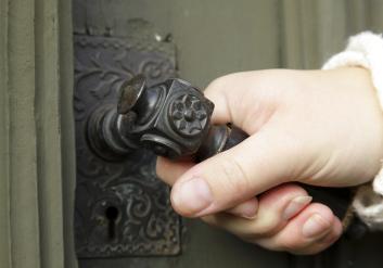 En hand håller i ett gammalt handtag. Handtaget sitter på en grön gammal dörr.