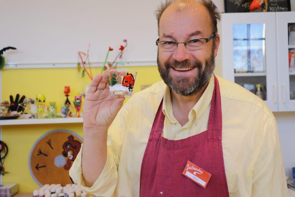 Pedagog och historiker Håkan Nordmark ler mot kameran och håller upp ett föremål som har tillverkats i den pedagogiska verkstaden. Föremålet är ett glas som någon har målat på.