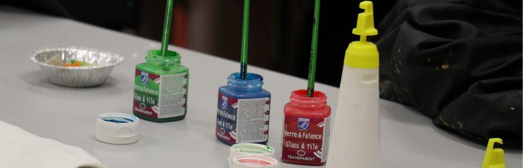 Färgburkar står uppradade redo för att börja användas av barnen som ska delta i Skapande skola