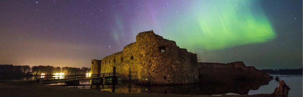 Fotografi förställande Kronobergs slottsruin. Bilden är tagen på kvällen och på himlen syns ett norrsken som skiftar i lila, blåa och gröna färger.
