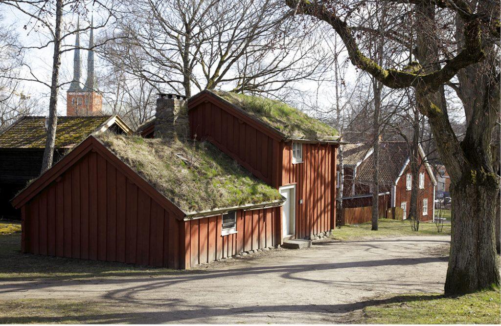 Fotografiet visar en röd stuga med mossa på taket. Stugan kallas för Högloftstugan och ligger i museikparken vid Smålands museum.