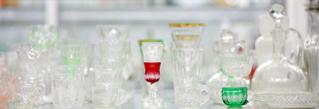 Dricksglas samlade på rad, de flesta i klarglas men ett är grönt och ett är rött.