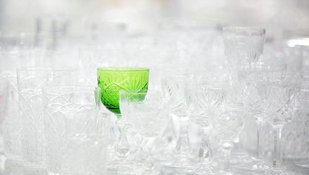Många glasföremål i klarglas och ett föremål i grönt glas