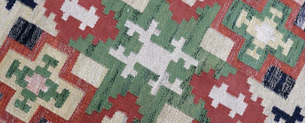 Detalj av en matta av Maja Andersson Wirde, en vävd matta i beige, röd och grönt.