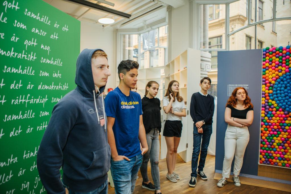 Elever står och lyssnar, förmodligen en guidning av utställningen.